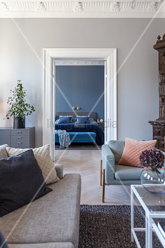 View through double doors into bedroom with grey-blue walls, bed and bedroom bench
