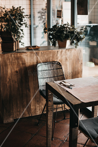 Table and chair in front of solid wooden cabinet with potted plants in dining area