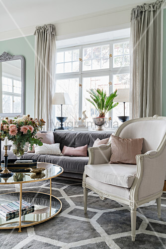 Stylish seating around round table in light-flooded living room with pastel-green walls