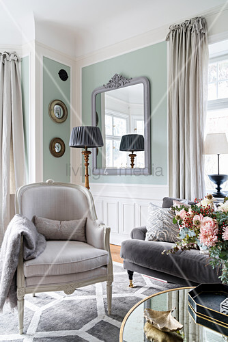 Armchair and sofa in light-flooded living room with pastel-green walls