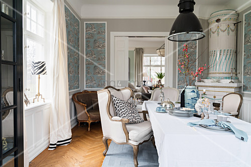 Stylish seating, tiled stove and patterned wallpaper in dining room