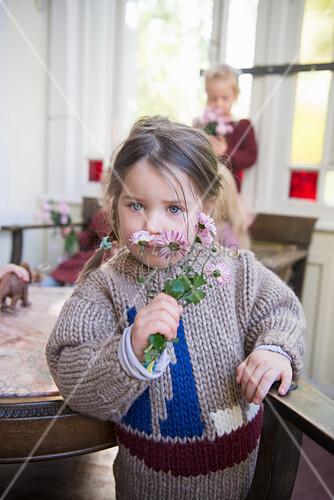 Mädchen im Strickpulli riecht am Blumensträußchen