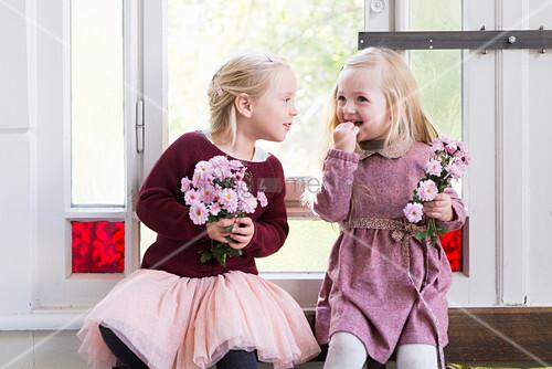 Zwei Mädchen mit Blumen am Altbaufenster mit Buntglas