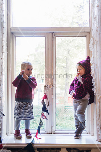 Two girls wearing sustainable fashion stood in period window