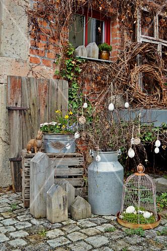 Vintage Milchkanne mit Osterdekoration, Holzhäuschen und Frühlingsblumen