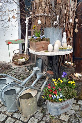 Österlich dekorierter Tisch, Giesskannen und Zinkwanne mit Frühlingsblumen
