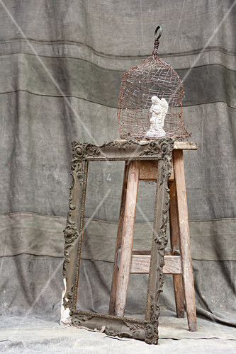 Angel figurine in cage on wooden stool and antique picture frame