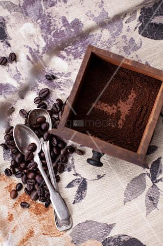 Schublade einer Vintage Kaffeemühle mit Kaffeepulver, daneben Kaffeebohnen und Löffel