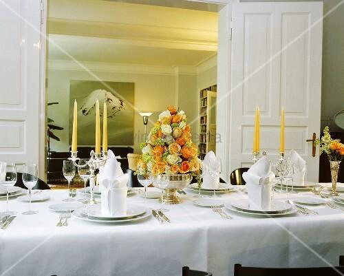 Festlich gedeckter Tisch mit Rosengesteck in Silberschale und Blick durch Flügeltür ins Wohnzimmer
