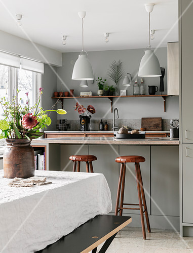 Dining table in front of open-plan kitchen in earthy shades