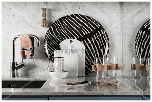 Glasses, chopping boards and zebra-patterned tray next to sink
