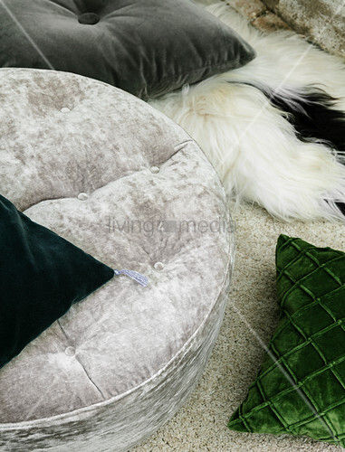 Velvet cushions in grey and green on fur blanket on rug