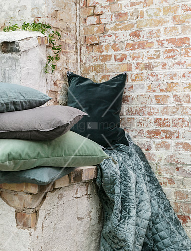 Velvet cushions and blanket in shades of green against brick wall