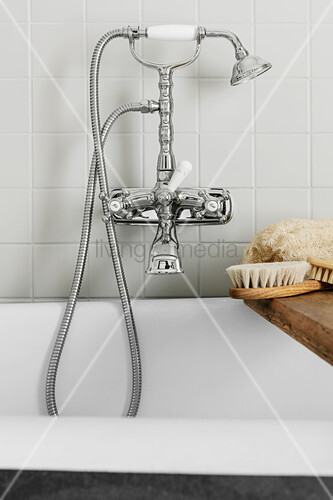Vintage-style tap fittings over bathtub with bath caddy