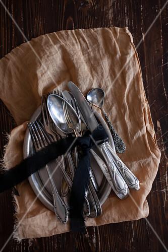 Tablett mit Silberbesteck mit Schleife auf braunem Tuch