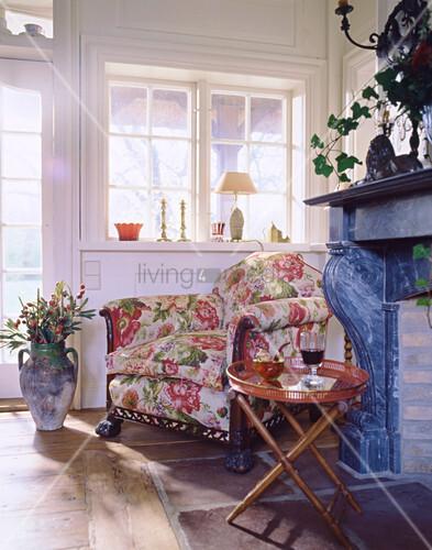 Geblümter Sessel vor offenem Kamin und Sprossenfenster