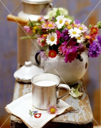 Stillleben mit Milch aus der Schweiz, Serviette und Blumen