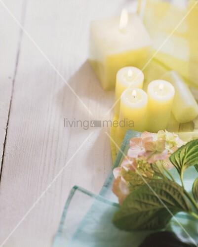 Stillleben mit brennenden Kerzen, Blüten und hellen Tüchern