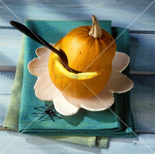 Hollowed-out pumpkin with spoon for Halloween pumpkin soup
