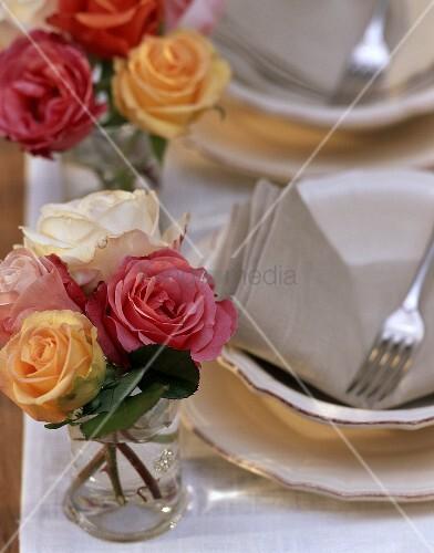 Kleine Rosensträusse auf gedecktem Tisch