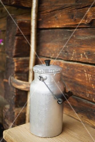 Nahaufnahme einer Milchkanne vor einem Blockhaus