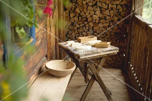 Bauernbutter und Holzmodeln auf einfachem Holztisch vor einer Berghütte