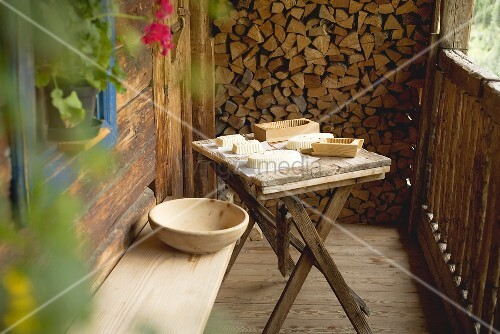 Farmhouse butter and wooden moulds on simple wooden table on veranda of Alpine chalet