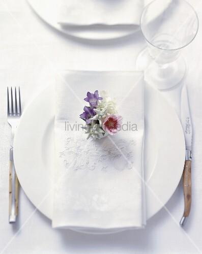 Ländliches Gedeck mit bestickter Serviette und Blüten