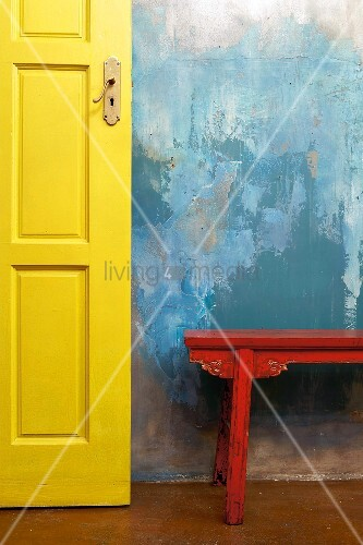 A patchy blue wall with yellow door