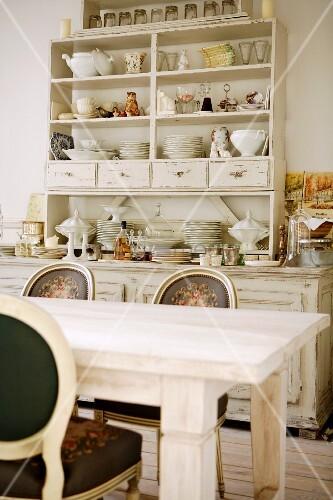 Antik weiss gestrichener Küchenschrank mit Geschirr und Deko