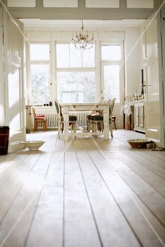 Blick durch Flügeltür in Wohnküche mit antiken Stühlen am rustikalen, weiss gestrichenen Esstisch
