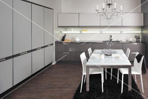 edelstahl esstisch mit wei er glasplatte und wei e lederst hle unter l ster in moderner k che. Black Bedroom Furniture Sets. Home Design Ideas