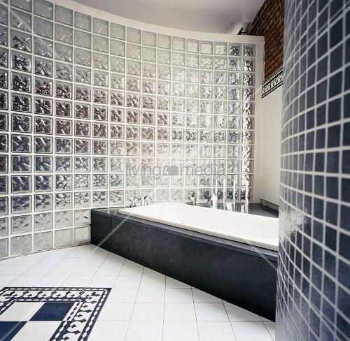 Loft-Badezimmer mit Wanne in steinverkleidetem Podest vor gebogener ...