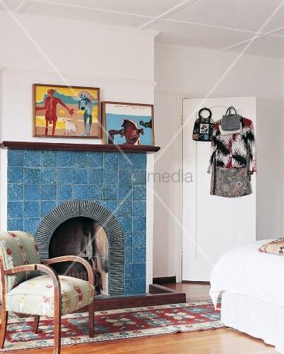offener blau gekachelter kamin in schlafzimmer mit teppichl ufer sessel und modernen bildern. Black Bedroom Furniture Sets. Home Design Ideas