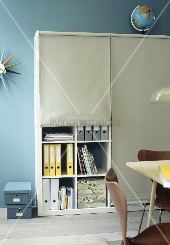 Home office: files on shelves hidden behind roller blinds