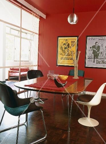 esstisch in roten raum mit glaswand designerst hlen rundherum und gerahmten filmplakaten an der. Black Bedroom Furniture Sets. Home Design Ideas