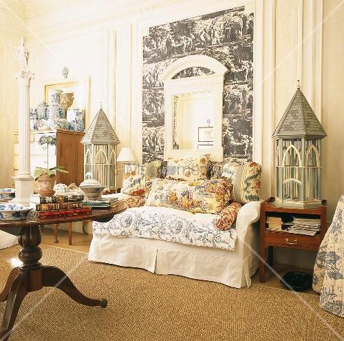 wei e couch mit bunten zierkissen zwischen zwei vogelk fige aus holztischen bild kaufen. Black Bedroom Furniture Sets. Home Design Ideas