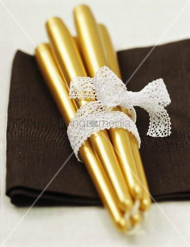 Goldene Kerzen für die weihnachtliche Tischdekoration