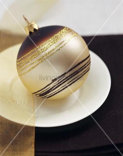 Eine braun-goldfarbene Christbaumkugel als Tischdeko