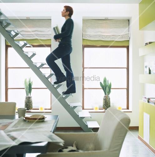 frau geht eine treppe in wohnraum ohne gel nder hoch. Black Bedroom Furniture Sets. Home Design Ideas