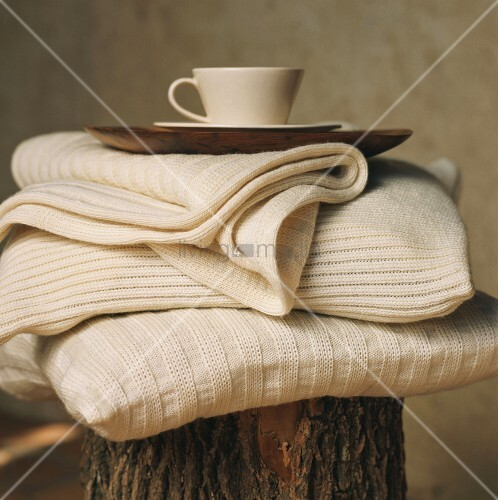 Woollen blankets and tray on tree stump