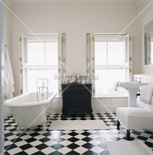 Ein Badezimmer mit Fliesenboden in Schachbrettmuster und freistehende Badewanne – Bild kaufen ...
