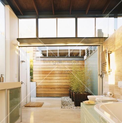 Freundliches Badezimmer mit Holzbalkendecke und Zugang zum Atrium ...