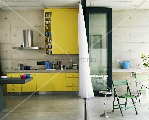 Eine knallgelbe Küchenzeile in einer Küche mit Betonwänden - durch eine Klapptür von der Terrasse getrennt