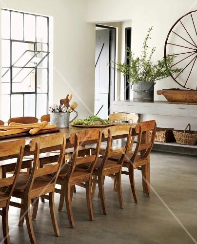 Biedermeierstühle an einem langen Esstisch mit Baguettes und Weintrauben