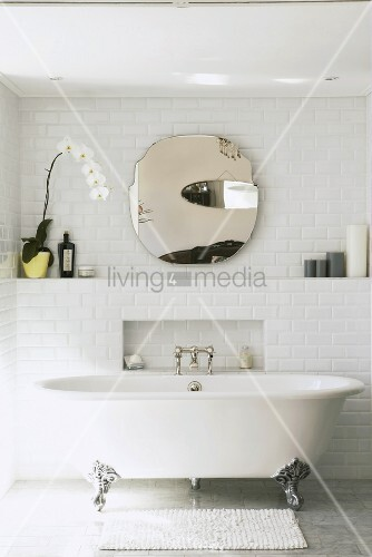 Antike Badewanne vor einer weissen Steinwand mit rundem Wandspiegel und Orchidee
