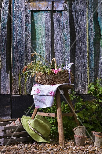 Basket of flowers on a stool outside a wooden cabin