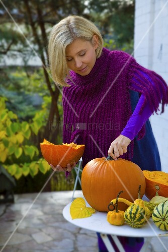 A woman on a terrace with pumpkins