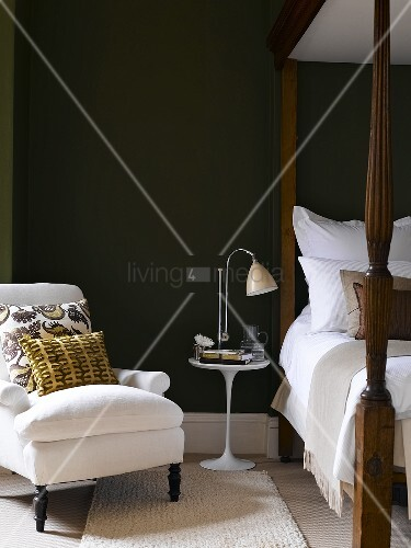 Bed, bedside table with lamp, upholstered chair in bedroom