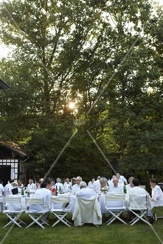 A party in a garden with people sat at white tables